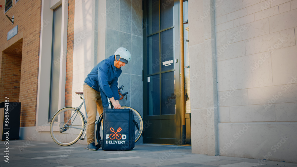 Fototapeta Food Delivery Man Wearing Thermal Backpack on Bike Delivers Restaurant Order, Leaving it Under the Door. Concept: Contactless (No Contact) Delivery for Social Distancing, Self Isolation