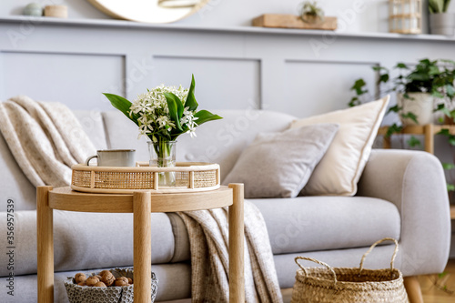 Fototapeta Scandinavian living room interior with design grey sofa, wooden coffee table, plants, shelf, spring flowers in vase, decoration and elegant personal accessories at home decor. obraz