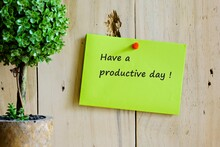 Conceptual Image Of Motivational Greeting. Text Have A Productive Day! On Sticky Note Push-pinned To Light Brown Wooden Wall.Focus On Note.