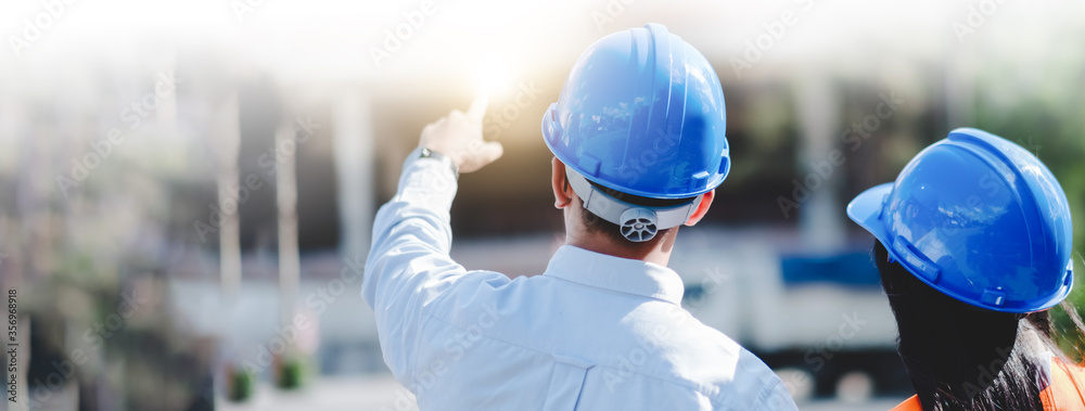 Fototapeta Asian man and woman engineer with the blue safety helmet meeting at the construction site.-panoramic banner