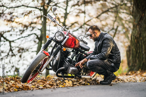 Obraz na plátně Bearded brutal man in sunglasses and leather jacket sitting on a motorcycle on t