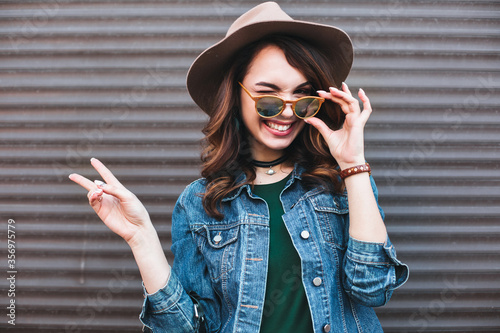 Cuadros en Lienzo Fashion, beautiful brunette in brown hat, making duck face and showing peace by two hands