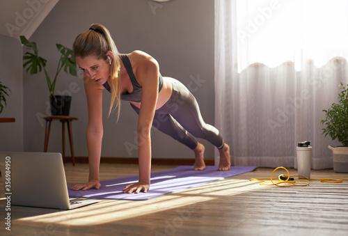 Fototapeta Young woman taking part in online fitness class obraz