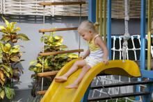 Active Toddler Girl On Slide. ...