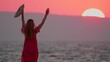 Silhouette of young slender girl in long dress flutters in wind, stands at sunset or dawn against background of sea, looks at big setting sun, waves her hand, hat to sun, says goodbye. Sea sunset.