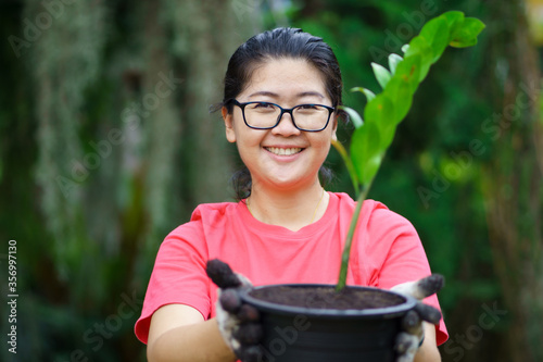 Photo New normal Happy gardener woman choose a tree to decorate the house
