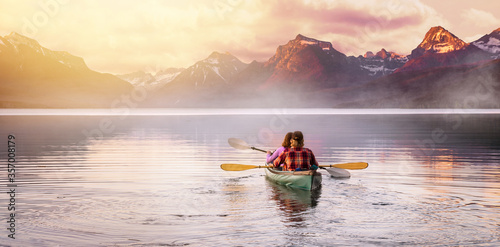 An adventurous couple in kayak paddle on a lake with rocky mountain background, Fototapet