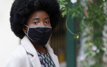 Fabric Face Mask In The Hand Of A Stylish Black Woman Wearing A Fancy Dress And A Coat. Face Coverings Are Recommended To Be Worn In COVID-19 Pandemic.