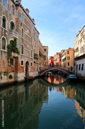 Fototapety, obrazy: Beautiful view of a canal between colorful stone buildings of Venice , Italy. There is a nice reflection of the street on the river.