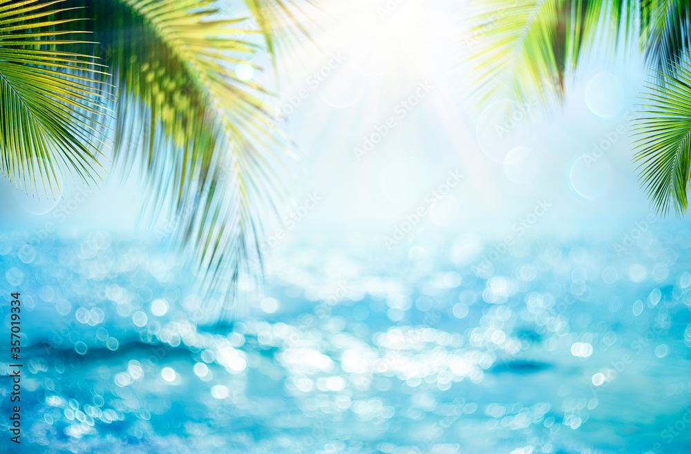 Fototapeta Blurred Blue Sky And Sea With Bokeh Light And Leaves Palm Tree - Summer Vacation Concept
