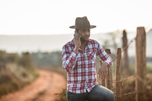 Farmer Or Country Man Using A Smartphone On The Farm. Internet 4G Farmer. Social Networks, Online Consultations.