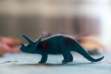 Fototapeta Dinusie - Selective focus of a blue toy rhinoceros on the table under the lights with a blurry background