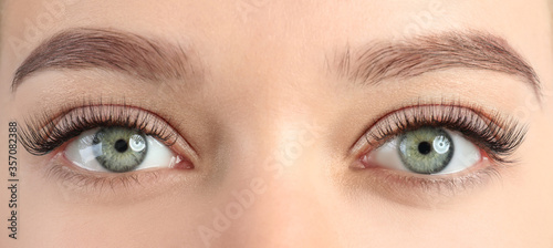 Fototapeta Young woman with beautiful eyelashes after extension procedure, closeup. Banner design obraz