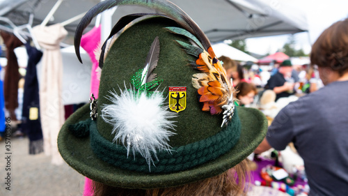 Photo Traditional green felt German alpine hat with rope twists and bright feathers