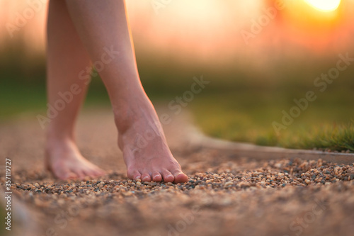 Fotografie, Obraz barefoot girl walking on the walkway ground stone with sunset light shine