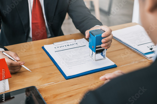 Fotografía Businessman stamping with approved stamp on document at meeting.