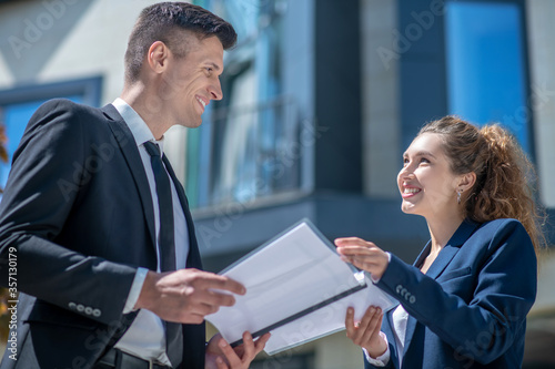 Smiling woman showing the documents to the client Canvas-taulu