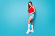 Leinwandbild Motiv Full size photo of attractive shiny chic girl feel cool confident on weekend holiday put hands pockets wear good look singlet footwear isolated over blue color background