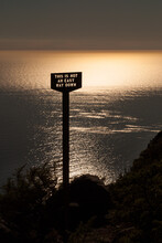 """Sunset Over The Sea With A Sign Reading """"This Is Not An Easy Way Down"""" At The Edge Of  Mountain"""