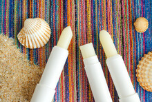 Three Lip Balms, Sunscreen Sticks On The Colorful Beach Towel With Sand And Seashells. Summer Lip Treatment And UV Protection Concept. Close Up, Flat Lay, Copy Space