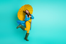 Full Size Profile Photo Of Attractive Funny Lady Good Mood Rainy Weather Hood Head Puddles Hold Big Yellow Umbrella Wear Raincoat Sweater Pants Gum Boots Isolated Teal Color Background