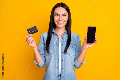 Fototapeta Close-up portrait of nice attractive lovely pretty confident cheerful girl holding hand device plastic card new solution novelty e-banking isolated bright vivid shine vibrant yellow color background obraz