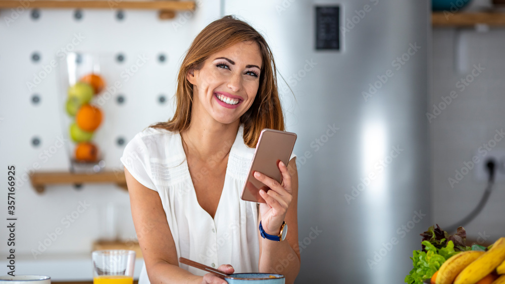 Happy woman using mobile phone during breakfast time in the kitchen. Young happy woman enjoying in morning time at the kitchen while text messaging on smart phone - obrazy, fototapety, plakaty