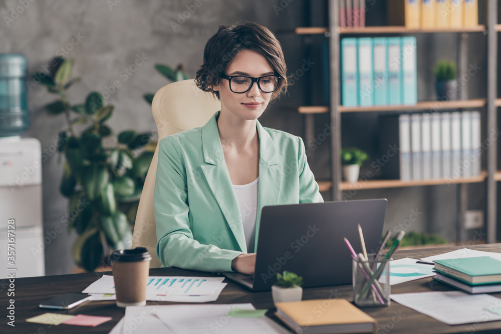 Fototapeta Focused girl agent lawyer manager sit desk chair work laptop have online communication colleagues boss read development company aim progress report wear blazer jacket in workplace workstation