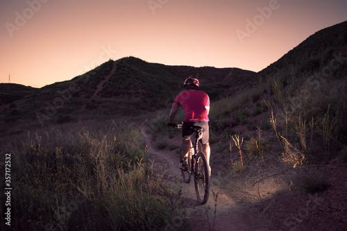 man riding a mountain bike at dusk Canvas Print