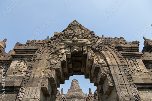 Kamala, one of the mythological watchers, guards, with his gaze, the arch over the passage between two levels of the Borobudur temple, in Central Java, Indonesia Fototapeta