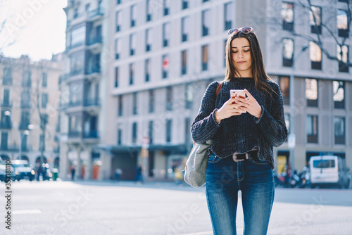 Portrait of cheerful brunette hipster girl in sunglasses walking in downtown on sunny weather Fototapet