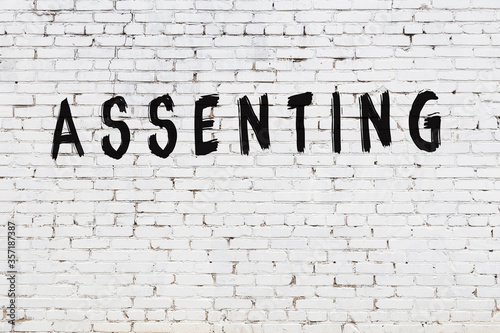 Photo Word assenting painted on white brick wall