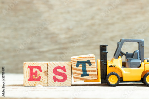 Photo Toy forklift hold letter block t to complete word EST (abbreviation of establish