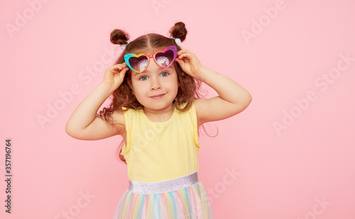 Obraz Portrait of surprised cute little toddler girl  in sunglasses over pink background.  Child model have fun and jump. Advertising childrens products - fototapety do salonu