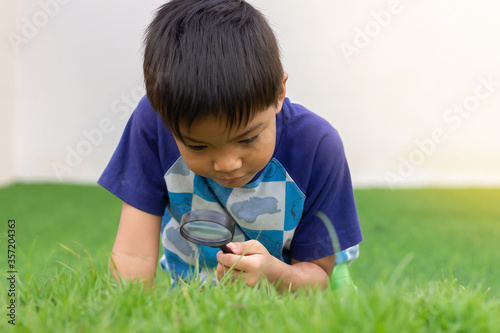 Portrait of happy Asian child boy holding and looking with magnifying glass on the flower tree and green grass field floor Canvas Print
