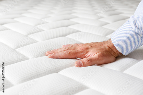 Fotografija Cropped shot of man testing white orthopedic matress on firmness