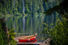 A Red Canoe Docks At The Mountain Lake In Tongass National Forest  Of Alaska. The Lake Is More Than 300 Feet Deep.