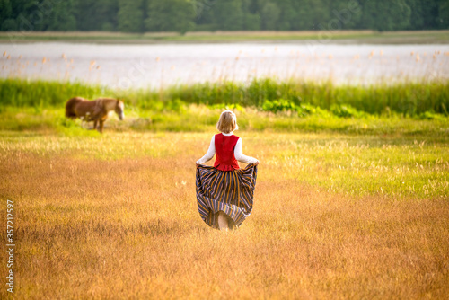 Tela Latvian woman in traditional clothing in field.