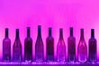 Leinwanddruck Bild - abstract empty wine bottles with purple led illumination