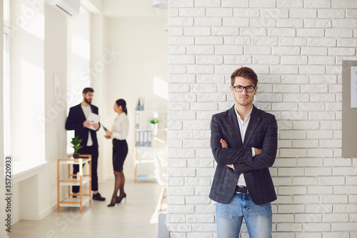 Photo Serious businessman in casual attire standing in a white office on a white wall