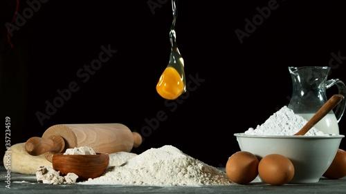 Freeze motion of falling raw egg into flour Fototapeta