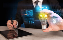 Businessman Holding Lightbulb With GROWTH HACKING Inscription, Online Security Idea Concept