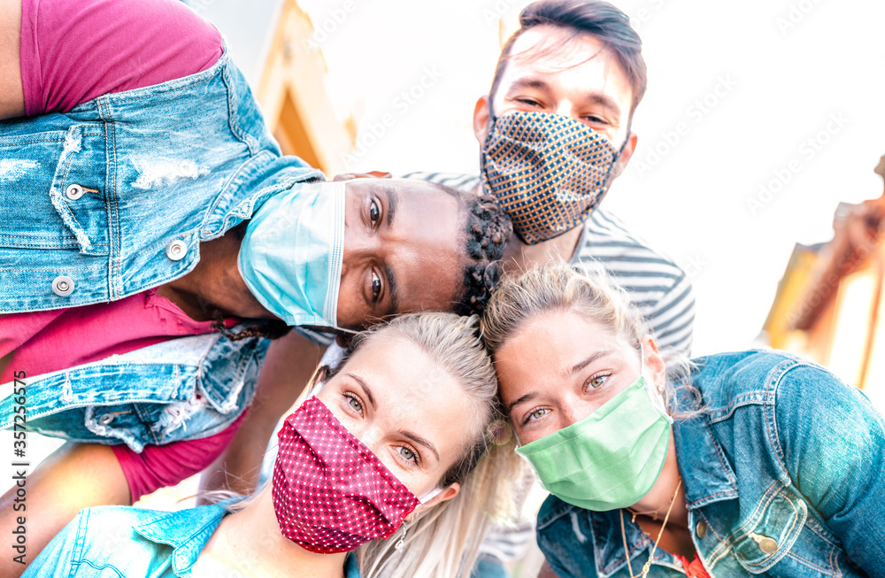 Fototapeta Multiracial millenial friends taking selfie smiling behind face masks - Happy friendship and new normal concept with young people having fun together - Bright sunshine filter with focus on left girl