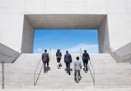 Tela Business people ascending modern stairs