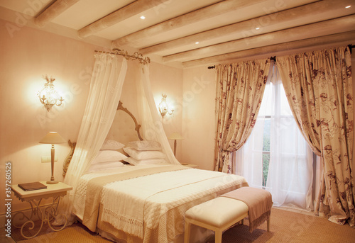 Fotografia Sconces and canopy above bed in luxury bedroom