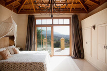 Bed With Canopy And French Doors Leading To Balcony In Bedroom