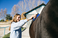 Cheerful Young Girl Standing And Using Brush On Big Chestnut Horse At Ranch