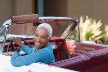Smiling Older Woman Driving Convertible