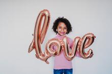 Portrait Of Smiling Girl Holding 'love' Foil Balloon