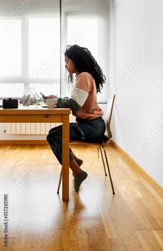 Young woman working from home using laptop and smartphone